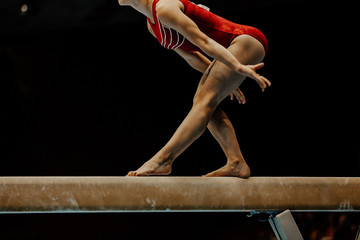Door stickers Gymnastics exercise balance beam female gymnast on black background