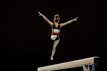 Door stickers Gymnastics balance beam split jump female gymnast on black background
