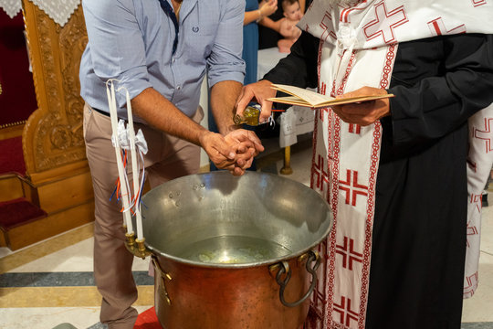 Orthodox priest puts oil in god father's hands in Baptism ceremony.