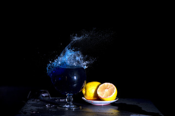 Accurate shot short and capacious in a glass with liquid.The breaking of a glass with fragments. The explosion of a glass on a black background with a colored liquid. Splashes of colors.