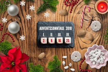 weihnachtliche Dekoration und Schiefertafel mit Würfeln und Datum aller Adventssonntage