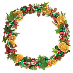 Christmas Wreath with candy canes, dried fruit, spice,  bauble decorations, natural winter leaf sprigs, holly berries, acorns and pine cones on white background. Christmas card for the festive season.