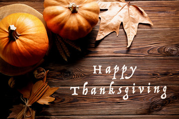 Happy thanksgiving concept. Still life composition with pumpkin and oher fruits and vegetble small decoration with funny font text white text. Wood textured table background. Top view, close up.