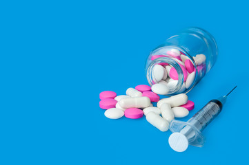 Syringe and glass jar with scattered white and pink pills on a bright blue background.