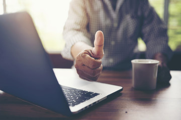 Close up businessman showing thumbs up with laptop