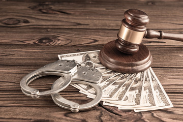 Judge's gavel, bills of American dollars, handcuffs for apprehending criminals on a wooden background. arrest, court, bail.