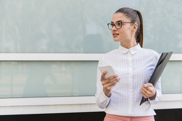 Successful young businesswoman using smartphone and holding documents outdoors.