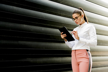 Pretty young woman with digital tablet by the office building