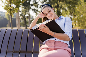 Beautiful  young woman  holding  open book and reading on bench in autumn park