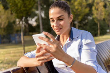 Young woman using mobile phone in the park