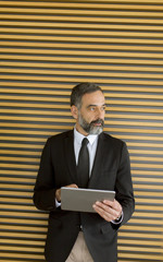 Middle age businessman with tablet in the office