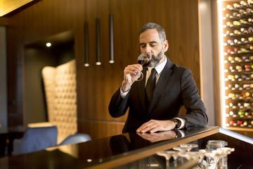 Senior handsome man drinking red wine