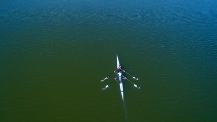 Boat coxed four rowers rowing on the tranquil lake. Aerial view of rowing and rowers.