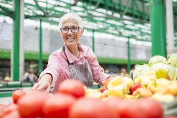 Senior woman sells vegetable on market