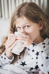Sick girl in bed with cup of tea, cold and flu season