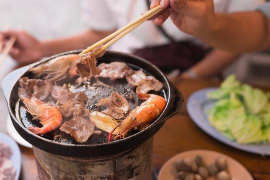 Asian girl is grilling pork in Korean style.