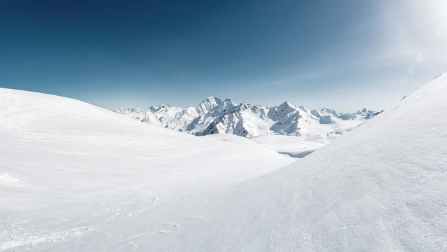 Sun over winter mountains covered with snow. Untouched freeride slope. Snow covered glacier