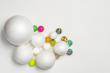 Eight white balls of plastic, different sizes and ten balls of the same size and different colors lie on a plane, on a flat background, in a dense composition, copy space.