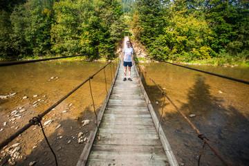 Tourist man walk by long wooden suspension bridge above river. balance concept