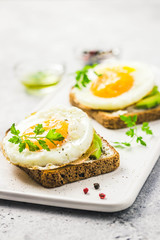 Avocado, cream cheese and fried egg sandwich. Selective focus, space for text.