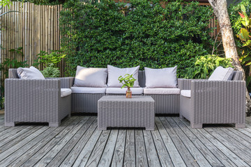 Fotobehang Tuin Large terrace patio with rattan garden furniture in the garden on wooden floor.