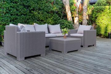 Large terrace patio with rattan garden furniture in the garden on wooden floor.