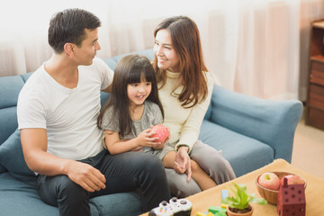 Family time young Parents and Daughter laughing which sit on sofa, daughter take an apple on hand which sit between father and mother which looking eye at home