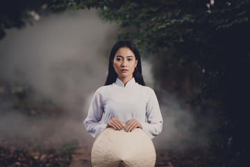 Ao Dai is traditional dress of vietnam, beautiful vietnamese woman in  white Ao Dai dress in the park