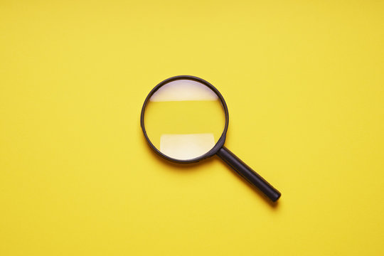 magnifying glass magnifier loupe search symbol on yellow background with copy space