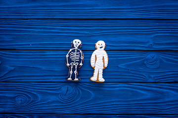 Halloween traditions. Halloween gingerbread in shape of evil characters on blue wooden background top view copy space