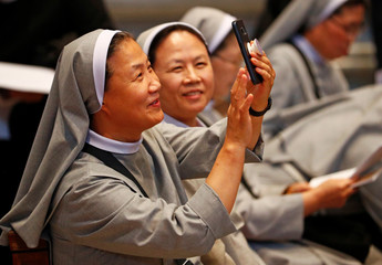 Korean nuns take pictures before the start of a special mass for peace in the Korean peninsula led by Italian cardinal Pietro Parolin in Saint Peter's Basilica at the Vatican