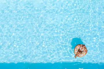 Woman on a donut buoy in a blue water swimming pool aerial view from above