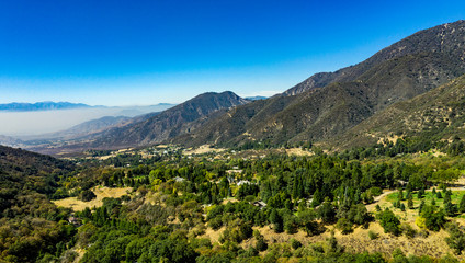 Aerial, drone view of Oak Glen located between the San Bernardino Mountains and Little San Bernardino Mountains with several apple orchards before the Fall color change