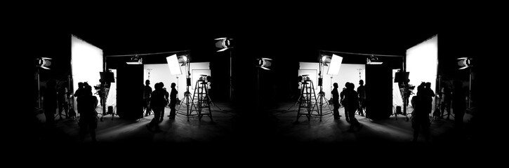Silhouette images of video production behind the scenes or b-roll or making of TV commercial movie that film crew team lightman and cameraman working together with director in big studio