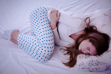 Young woman suffering from abdominal pain while sitting on bed at home.