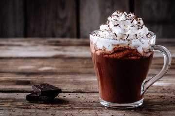 Fotobehang Chocolade Hot chocolate drink with whipped cream in a glass on a wooden background
