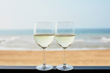 Two glasses of white wine with Atlantic coast beach in background