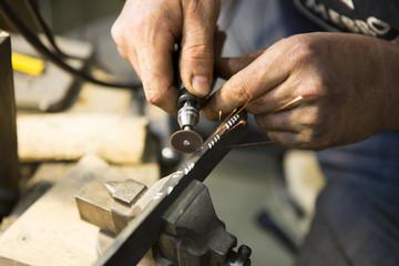 Artisan en train de graver une lame de couteau