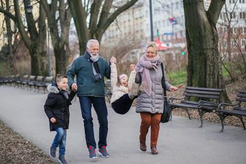 Grandparents having fun with their grandchildren in city park.