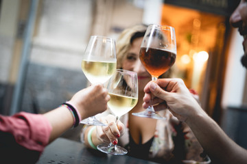 Group of friend toast with red and white wine. Main focus on one of the glasses, blurred background