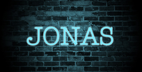 first name Jonas in blue neon on brick wall