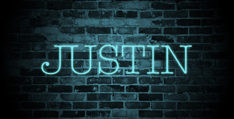 first name Justin in blue neon on brick wall