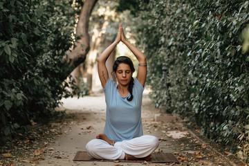 Unrecognizable female doing yoga on garden path