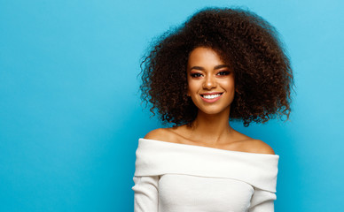 Wall Mural - Beautiful black woman with white teeth smiling isolated on blue background