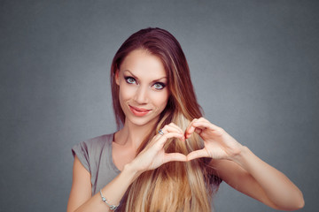 woman making a heart gesture with her fingers hands