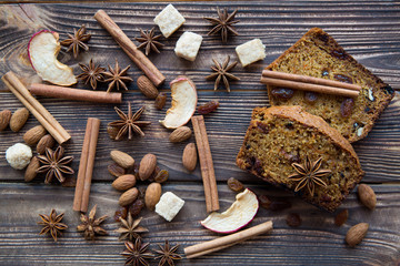 Christmas background, carrot pumpkin cake slices with cinnamon, almonds, nuts, anise stars and dried apples slces on brown wooden background, top view. Brown cane sugar pices.