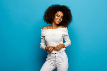 Wall Mural - Beautiful black woman with white teeth and afro is smiling isolated on blue background