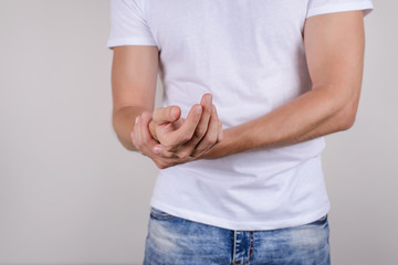Cropped close up photo portrait of unhappy sad upset stressed unsatisfied guy holding palm in hand isolated on grey background wear casual white t-shirt denim jeans