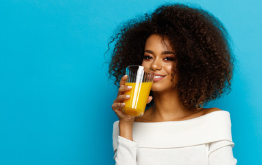 Wall Mural - Beautiful african american girl with copy space drinking a orange juice