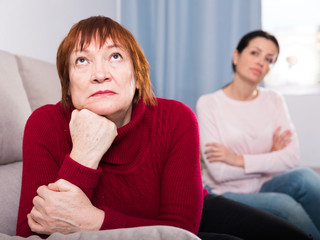 Unhappy women sitting at sofa after conflict at home